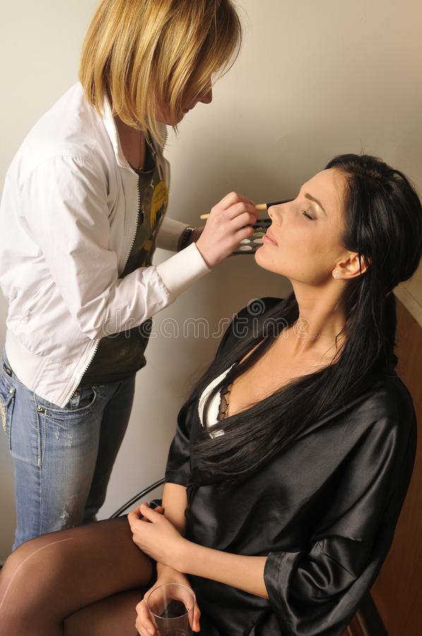 Makeup Artist Applying Makeup To Brunette Model Royalty Free Stock Photo