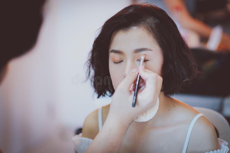 Makeup artist applying pink eyeshadow to beautiful Asian model. White, girl, face, skin, beauty, woman, fashion, background, powder, brush, female, mascara royalty free stock photos