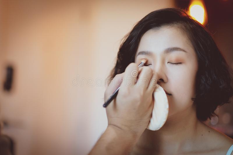 Makeup artist applying pink eyeshadow to beautiful Asian model. White, girl, face, skin, beauty, woman, fashion, background, powder, brush, female, mascara stock photos