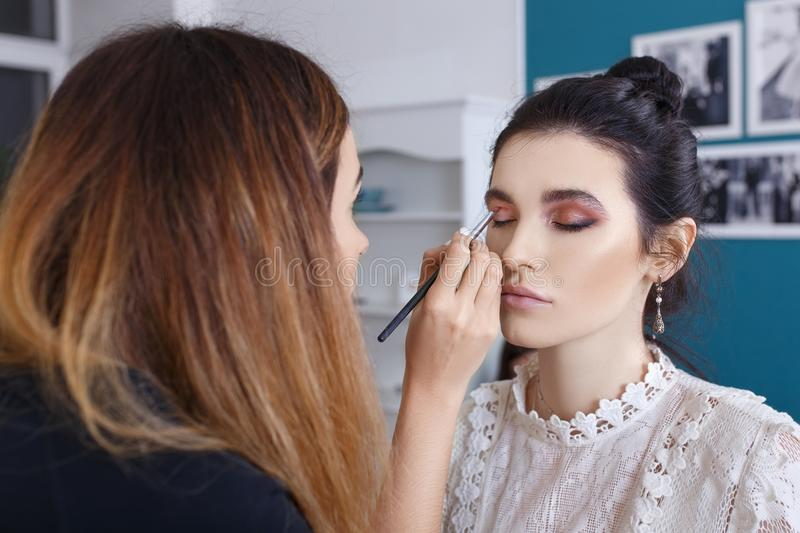 Makeup artist applying shadows on the eyelid royalty free stock images