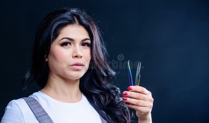 Makeup artist. Cosmetic tweezer. Girl makeup face hold tweezer for eyelash extension. Beauty shop concept. Makeup false royalty free stock photos