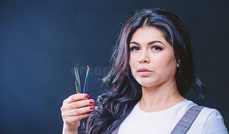 Makeup artist. Cosmetic tweezer. Girl makeup face hold tweezer for eyelash extension. Beauty shop concept. Makeup false stock images