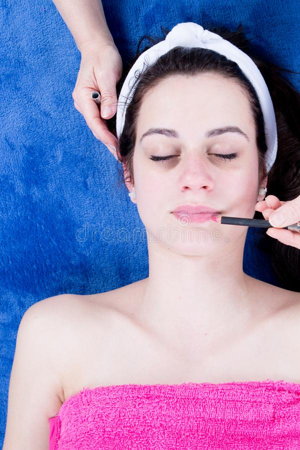 Makeup artist creating beautiful makeup for brunette pretty young stock photo