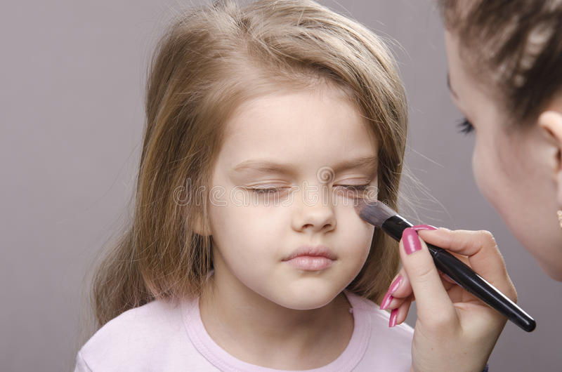 Makeup artist deals powder on face of girl royalty free stock photo
