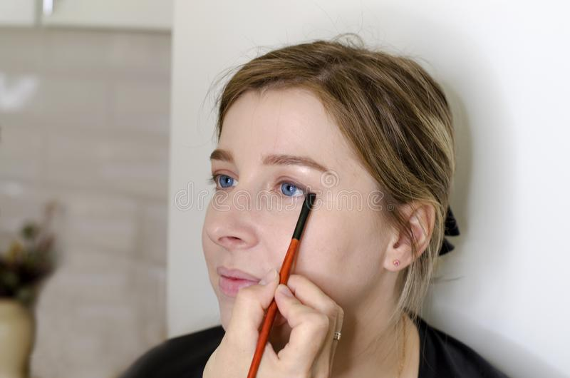 The makeup artist does makeup for the girl stock image