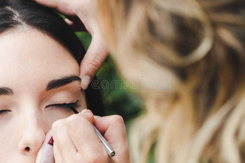 A makeup artist is drawing the eye line to a model. It is a close up image royalty free stock photos