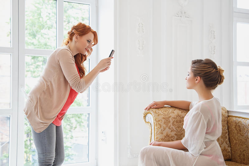 Makeup artist and hair stylish making photo of beautiful bride on her smartfone stock image