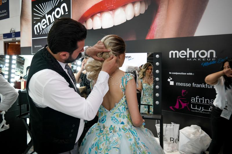 Makeup artist and hairstylist applying professional makeup on a young blond woman in a colorful dress stock photography