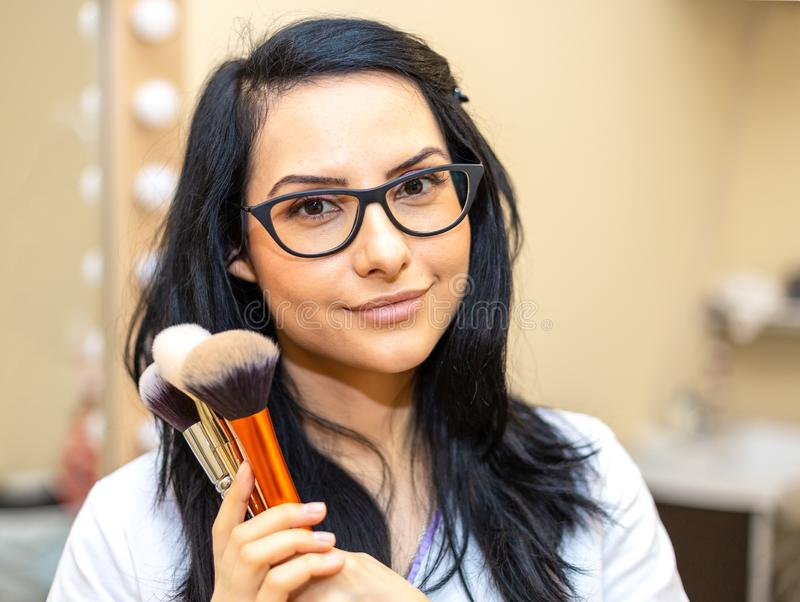Makeup artist holding brushes. Makeover. Perfect Skin royalty free stock image