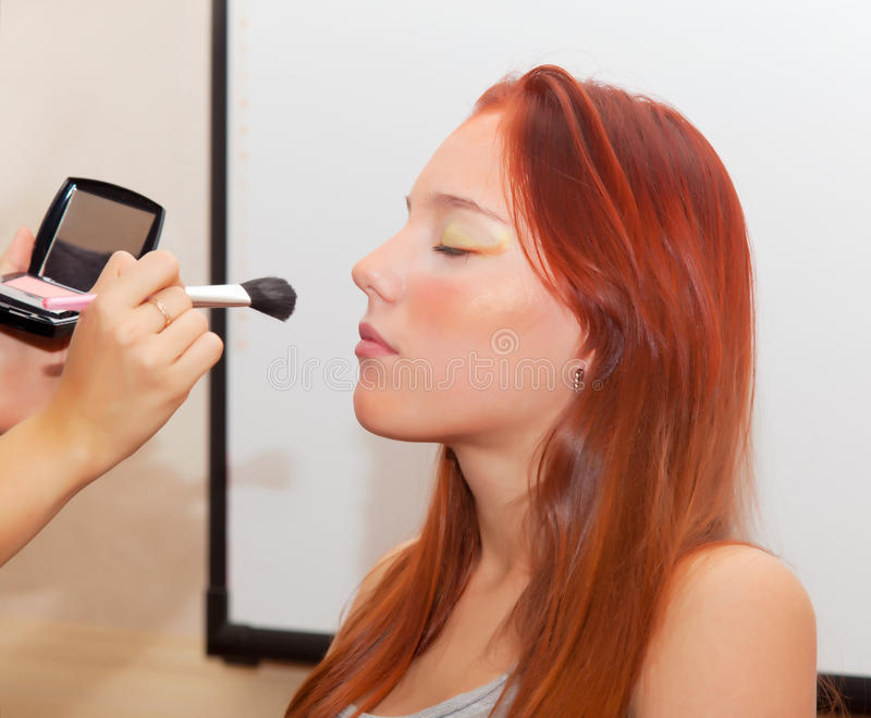 Makeup artist make-up girl with eyes closed. Beauty salon royalty free stock photography