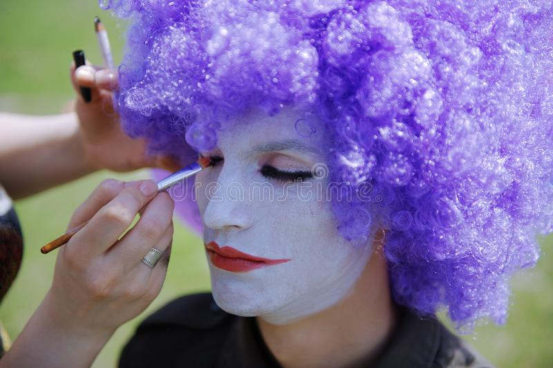Makeup artist making clown face painting to the actor stock image
