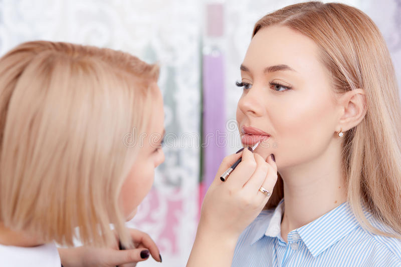 Makeup artist making makeup of lips. royalty free stock images