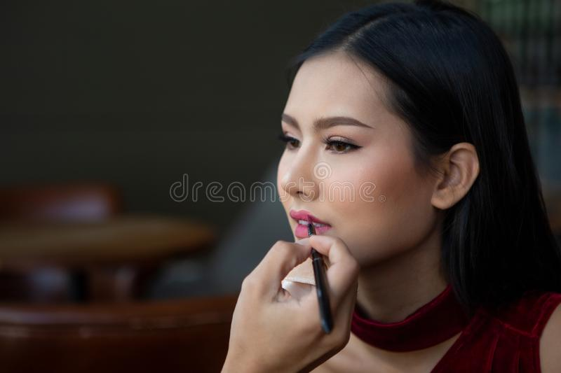 Makeup artist man applies lipstick painting lips of young beauty model on Backstage , asian woman royalty free stock images