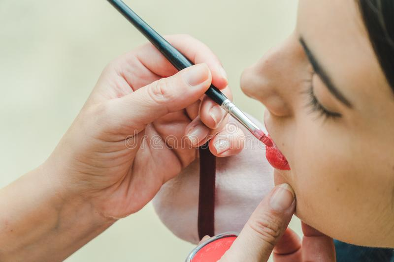 A makeup artist is painting the lips to a model. It is a close up image royalty free stock photo