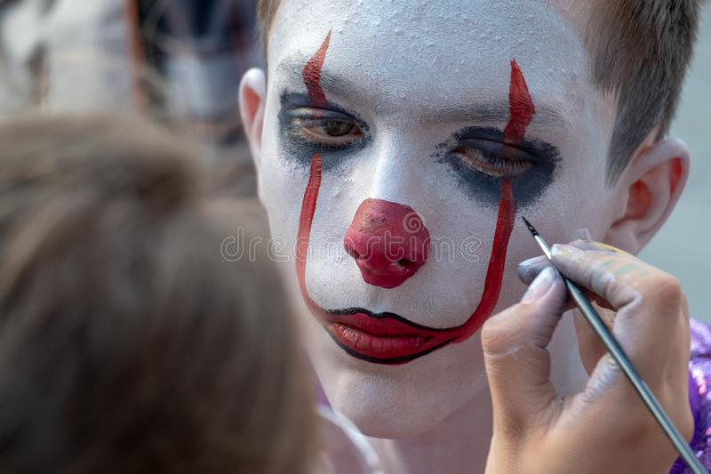 Street makeup for halloween. A makeup artist paints a clown`s face to a teenager guy like Pennywise. A man in the image of IT on stock photos