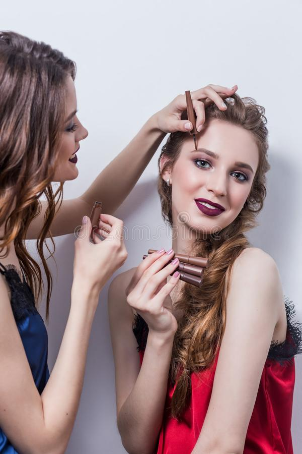Makeup artist paints the eyebrow of a beautiful girl, blonde, brown eyeliner, she grins and holds her hand on the makeup, white ba royalty free stock photos