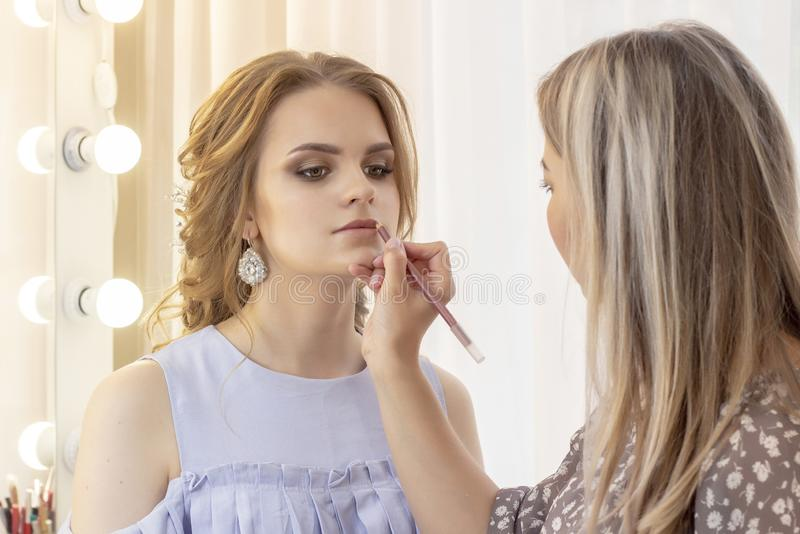 Makeup artist paints lips model with lip liner. make-up in gentle day neutral beige shades. Wedding, meet royalty free stock image