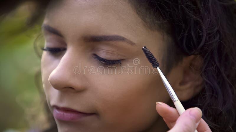 Makeup artist preparing beautiful young woman for shoot, enhancing eyebrows stock image