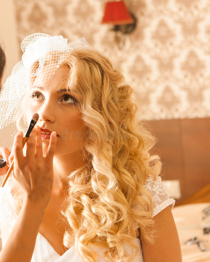 Makeup artist preparing bride before the wedding in a morning royalty free stock image