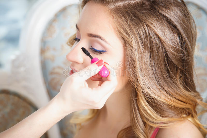 Makeup artist preparing bride before the wedding in a morning royalty free stock photo