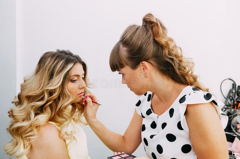 Makeup artist preparing bride before the wedding in a morning royalty free stock images