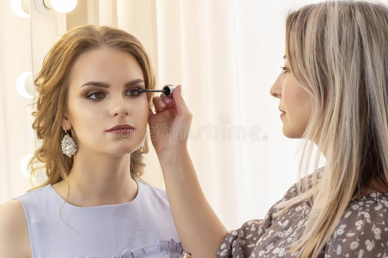 Makeup artist puts makeup on girl model. applies mascara on eyelashes. beautiful girl model, portrait. Nude colors in makeup. wedd stock photography