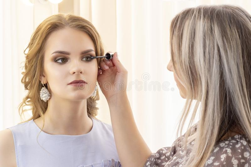 Makeup artist puts makeup on girl model. applies mascara on eyelashes. beautiful girl model, portrait. Nude colors in makeup. wedd royalty free stock photography