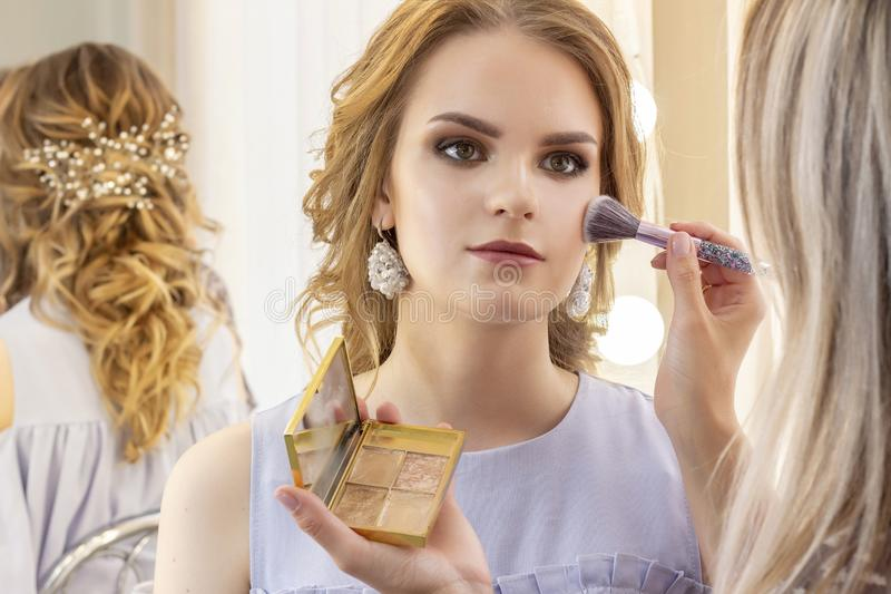 Makeup artist puts makeup on girl model. Brush powder on cheekbones and face. beautiful girl model, portrait. Nude colors in makeu royalty free stock photo
