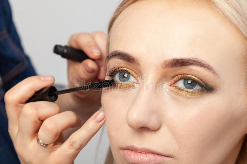 Makeup artist puts on an oriental-style make-up with gold and green shades of a young attractive blonde girl, paints her eyelashes royalty free stock photography