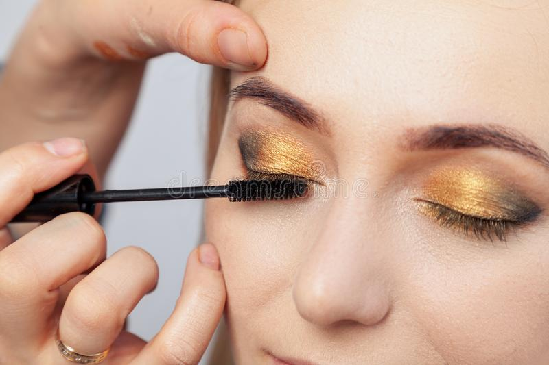 Makeup artist puts on an oriental-style make-up with gold and green shades of a young attractive blonde girl, paints her eyelashes stock image