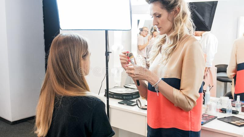 Professional makeup artist standing at young model in beauty salon royalty free stock image