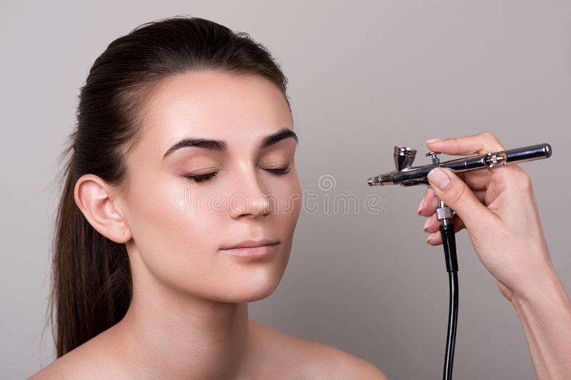 Makeup artist using airbrush. Fashion brunette model with hair tail over gray background. Professional makeup with aerograph. Girl royalty free stock image