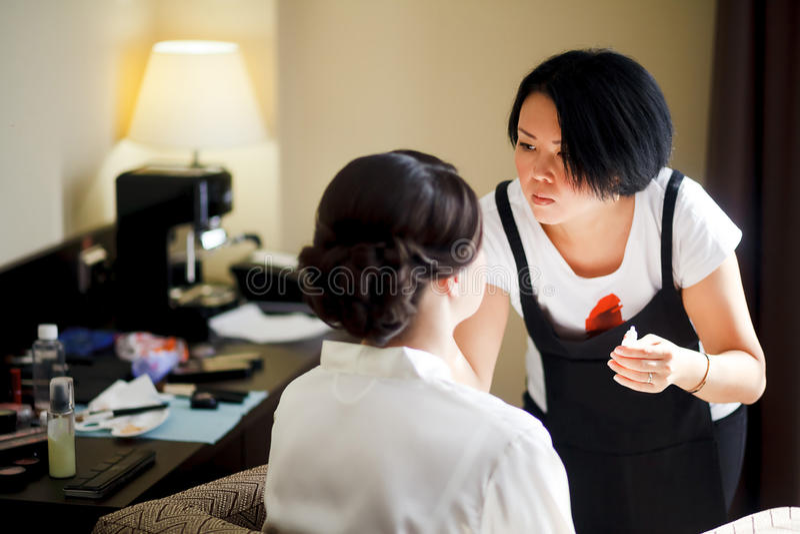 Makeup artist at work, asian woman doing makeup for bride, in morning. Wedding preparations. stock photos