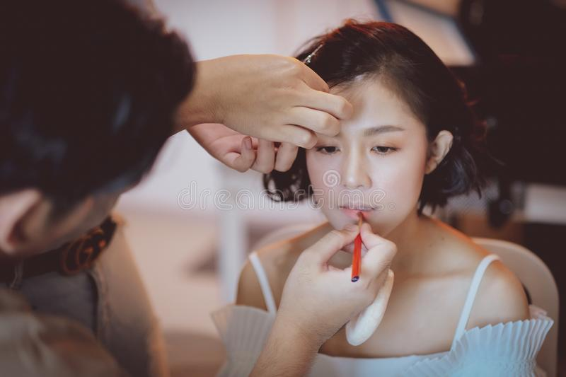Makeup artist working on beautiful Asian model. Beauty, fashion, female, face, girl, professional, woman, style, person, young, people, hair, studio, applying royalty free stock photo