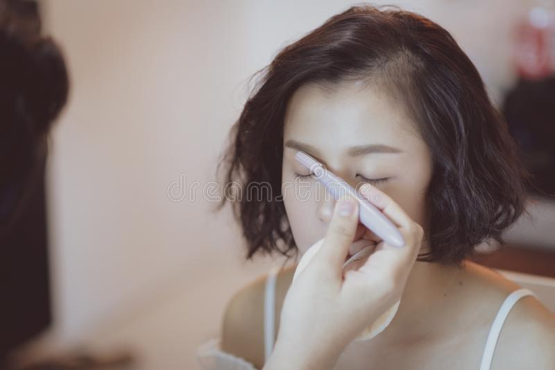 Makeup artist working on beautiful Asian model. Beauty, fashion, female, face, girl, professional, woman, style, person, young, people, hair, studio, applying royalty free stock photos