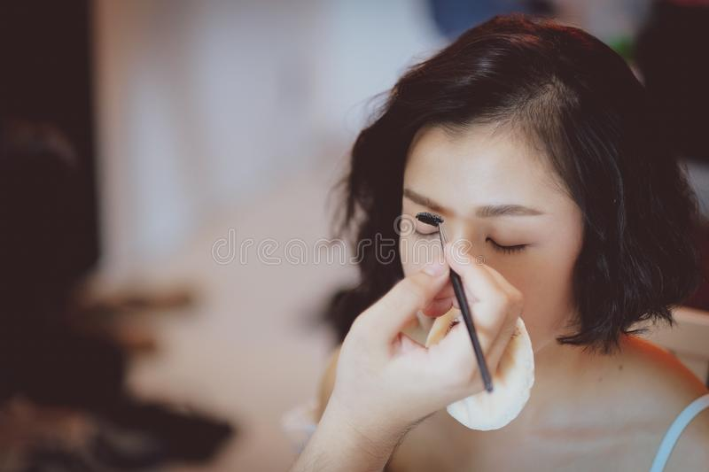 Makeup artist working on beautiful Asian model. Beauty, fashion, female, face, girl, professional, woman, style, person, young, people, hair, studio, applying stock photo
