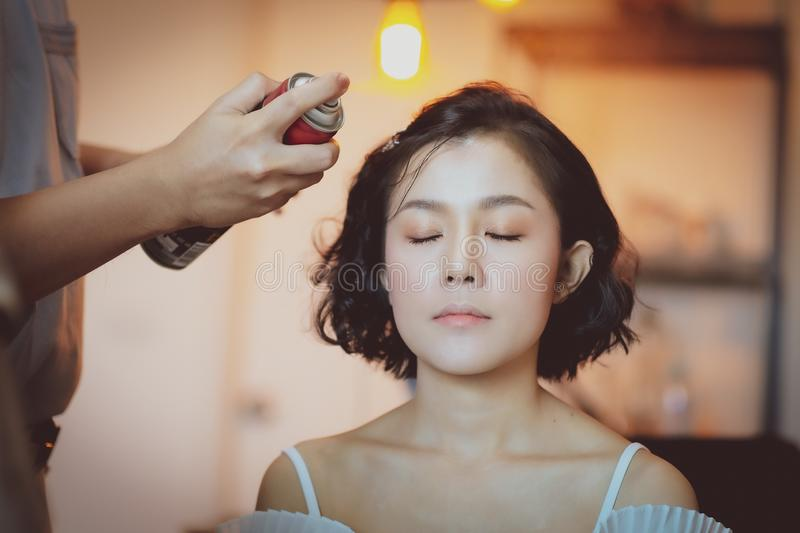 Makeup artist working on beautiful Asian model. Beauty, fashion, female, face, girl, professional, woman, style, person, young, people, hair, studio, applying royalty free stock image