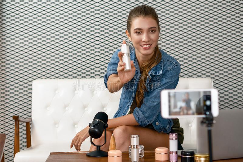 Makeup artist youtuber demonstrating her cosmetic product live online. A makeup artist youtuber demonstrating her cosmetic product live online stock image