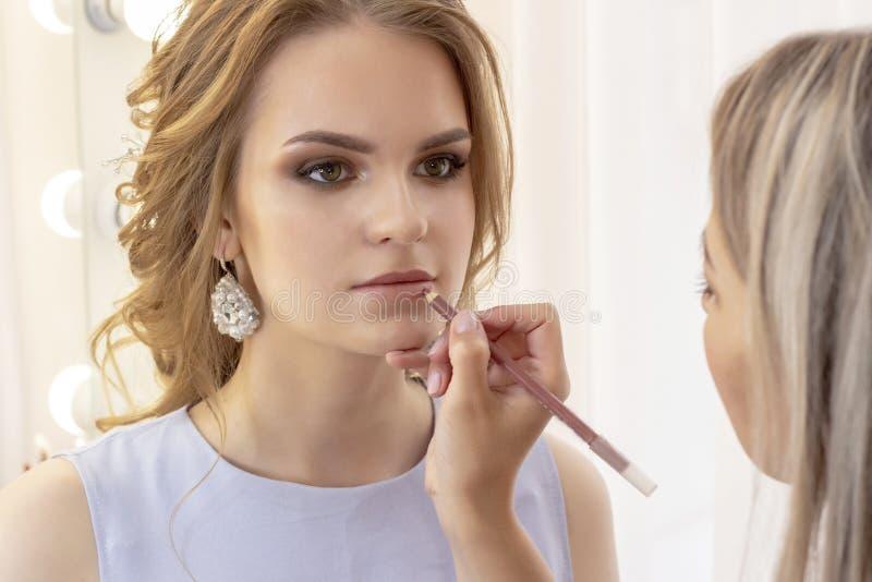 Makeup artysta maluje wargi modeluje z warga liniowem makijaż w delikatnego dnia beżu neutralnych cieniach obraz stock