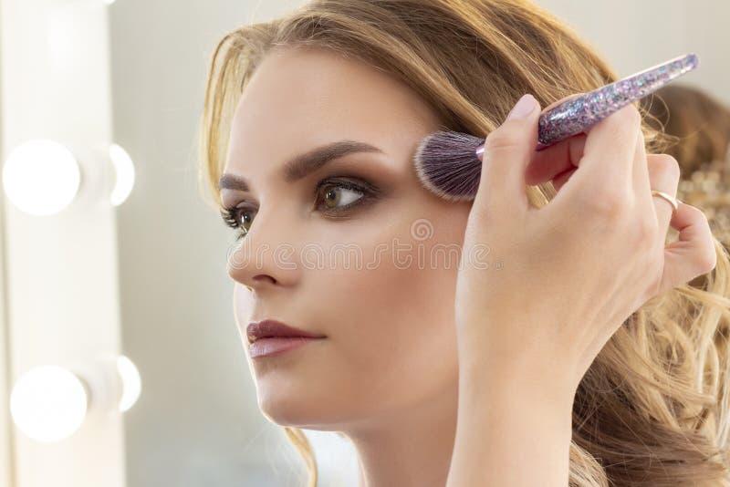 Makeup artysta stawia makeup na dziewczyna modelu Muśnięcie stosuje cienie, concealer piękny dziewczyna model, portret Naga posta zdjęcia royalty free