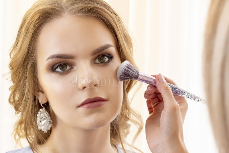 Makeup artysta stawia makeup na dziewczyna modelu Muśnięcie stosuje cienie, concealer piękny dziewczyna model, portret Naga posta zdjęcie stock