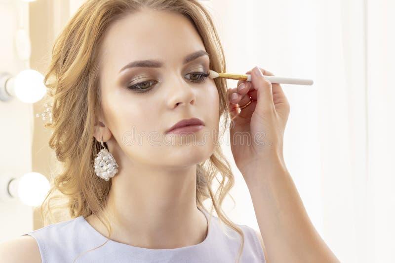 Makeup artysta stawia makeup na dziewczyna modelu Muśnięcie stosuje cienie, concealer piękny dziewczyna model, portret Naga posta fotografia royalty free