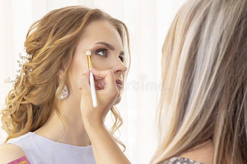 Makeup artysta stawia makeup na dziewczyna modelu Muśnięcie stosuje cienie, concealer piękny dziewczyna model, portret Naga posta obraz stock