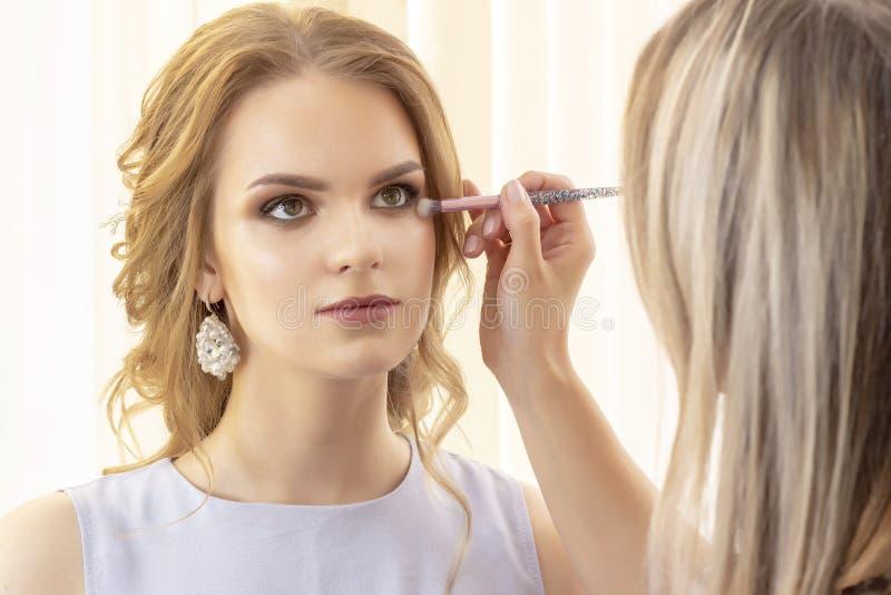 Makeup artysta stawia makeup na dziewczyna modelu Muśnięcie stosuje cienie, concealer piękny dziewczyna model, portret Naga posta obraz royalty free