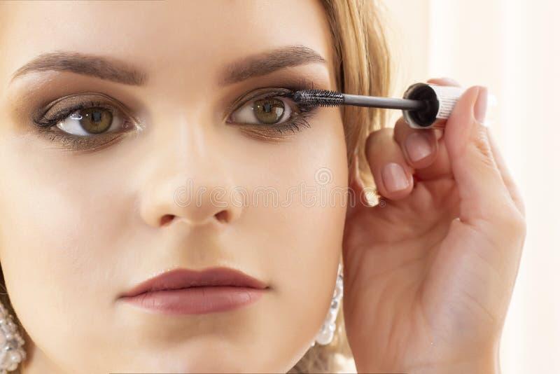 Makeup artysta stawia makeup na dziewczyna modelu stosuje tusz do rzęs na rzęsach piękny dziewczyna model, portret Naga postać ko obraz stock