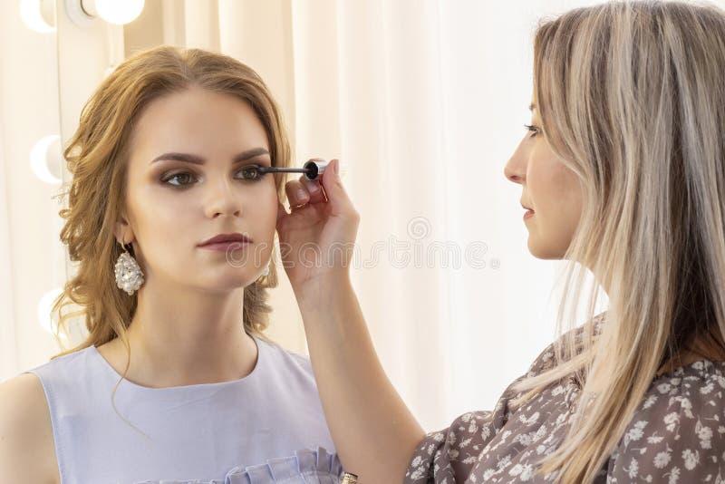 Makeup artysta stawia makeup na dziewczyna modelu stosuje tusz do rzęs na rzęsach piękny dziewczyna model, portret Naga postać ko fotografia stock