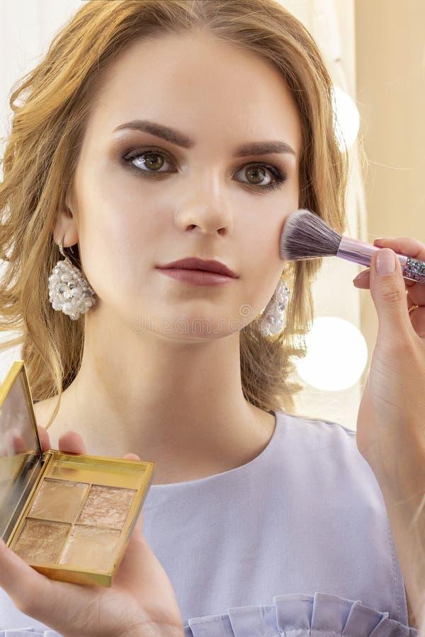 Makeup artysta stawia makeup na dziewczyna modelu Szczotkarski proszek na cheekbones i twarzy piękny dziewczyna model, portret Na obrazy stock