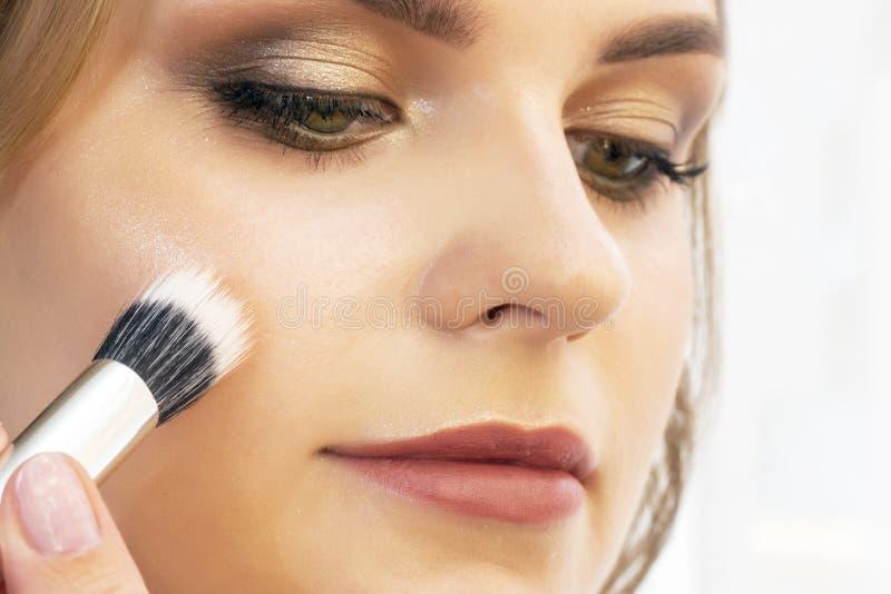 Makeup artysta stawia makeup na dziewczyna modelu Szczotkarski proszek na cheekbones i twarzy piękny dziewczyna model, portret Na zdjęcie royalty free