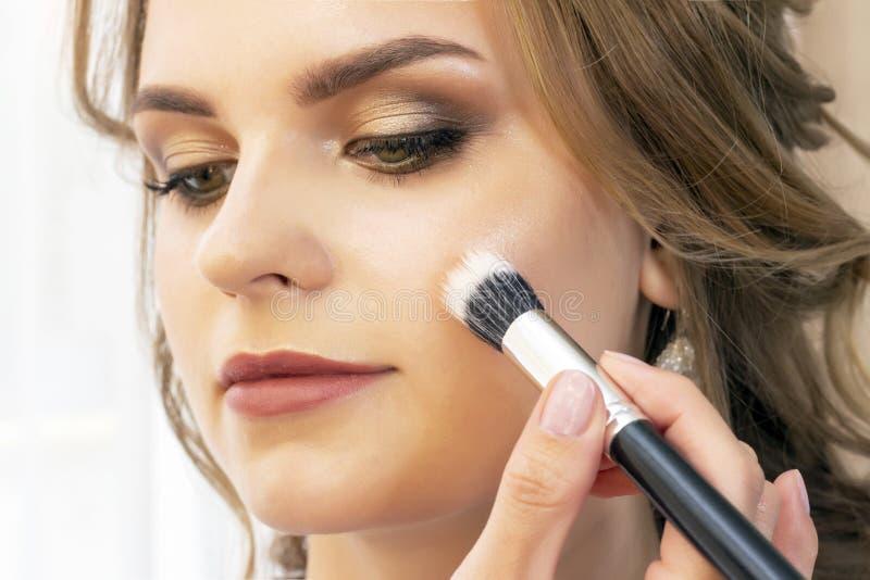 Makeup artysta stawia makeup na dziewczyna modelu Szczotkarski proszek na cheekbones i twarzy piękny dziewczyna model, portret Na zdjęcia stock