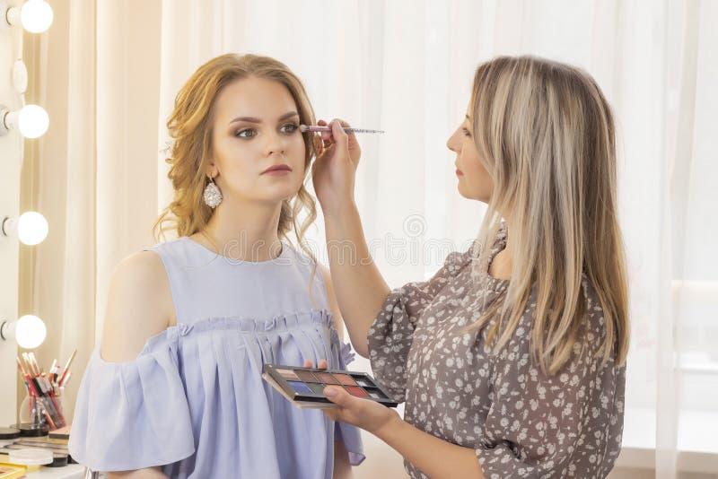 Makeup artysta stawia uzupełnia na dziewczyna modelu ślubny makeup, naturalny makeup makijażu artysta stawia oko cień na powiekac obrazy royalty free